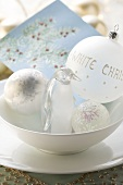 Christmas decorations (baubles and penguin) in a bowl