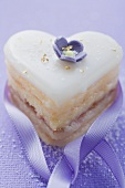 Small heart-shaped cake with sugar flower, gold and ribbon