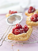 Raspberry puff pastry tarts with sugar on cake rack