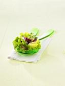 Mixed salad leaves on salad servers