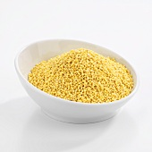 Organic golden millet in white bowl