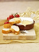 Camembert in terracotta dish with baguette slices