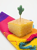 Cube of cornbread with cactus cocktail stick on cloth (Mexico)