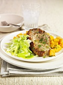Pork chop with herb butter and vegetables