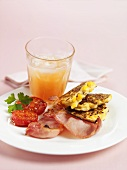 Sweetcorn cakes with bacon & tomato, glass of fruit juice