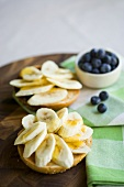 Banana slices and honey on bread roll, dish of blueberries