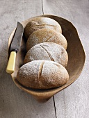 Four loaves of organic bread in wooden bowl with knife