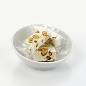 Individually packed pieces of almond nougat in white bowl
