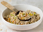 Pearl barley with vegetables in bowl with wooden spoon