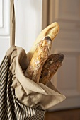 Baguettes in fabric bag on an apartment door (close-up)