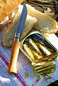 Opened sardine tin and baguette on newspaper (France)