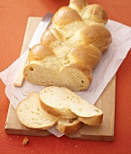 Bread plait, partly sliced, on chopping board