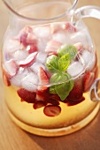 Strawberry punch with basil in a glass jug