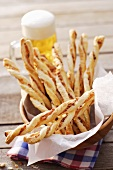 Spicy cheese straws in wooden bowl, glass of beer