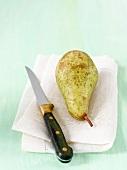 Eine Birne auf Stoffserviette mit Messer