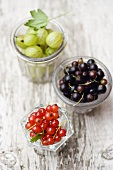 Blackcurrants and gooseberries in glass dishes