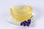 Lavender tea in glass cup, lavender flowers in saucer
