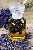 Lavendelöl in Apothekerflasche, umgeben von Lavendelblüten
