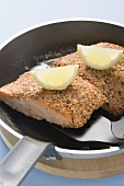 Fried salmon fillet with lemon wedges in frying pan