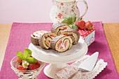 Biskuitrolle mit Erdbeeren und Schokoglasur auf Tortenständer
