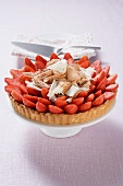 Strawberry tart with chocolate shavings on cake stand
