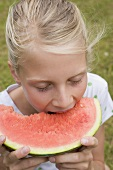 Girl eating watermelon out of doors