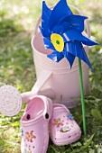 Windrad, Giesskanne und Kinderschuhe im Garten