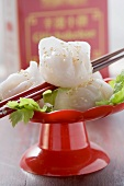 Dim sum with sesame seeds on coriander leaves (China)