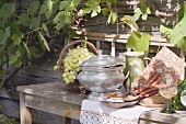 Still life with grapes, bread, sausages & wine in front of farmhouse