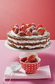 Strawberry cream cake on cake stand, strawberries, icing sugar
