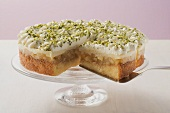 Apple cake with cream and pistachios, a piece cut