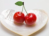Pair of marzipan cherries in heart-shaped mother-of-pearl dish
