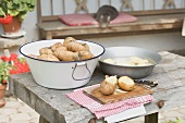 Potatoes, partly peeled, on table in front of farmhouse