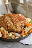 Roast pork with root vegetables in a frying pan