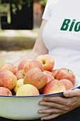 Woman holding a bowl of fresh organic apples