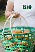 Woman carrying potatoes in a plastic basket