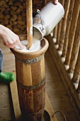 Pouring milk into a butter churn