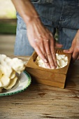 Hands pressing farmhouse butter into wooden mould