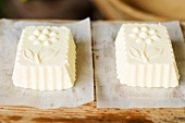 Blocks of butter shaped in wooden moulds on paper