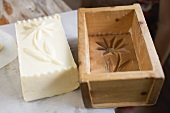 Butter with flower design beside wooden mould