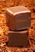 Two Dominosteine (chocolate-coated layered gingerbread) on cocoa