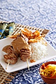 Chicken satay kebabs with peanut sauce, rice and crisps