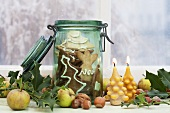 Spekulatius (German Christmas shortcrust biscuits) in a preserving jar with candles, apples and nuts