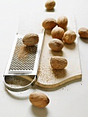 Nutmeg seeds with a grater on a chopping board