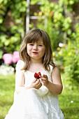 Kleines Mädchen isst Erdbeere im Garten