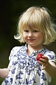 A little blonde girl holding a strawberry
