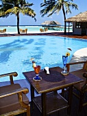 Two cocktails on a wooden table next to a pool with a view of the sea