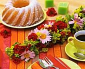 Kaffeetisch mit Blumengirlande und Gugelhupf