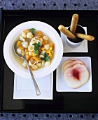 Noodle soup with vegetables, bread sticks and peach slices