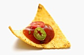 Tomato and pepper dip on tortilla chip